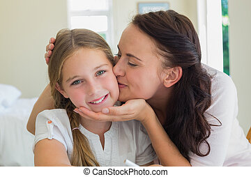 Mother kissing daughter at home - Loving mother kissing...