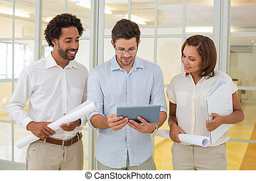 Three young business colleagues using digital tablet with blueprints in the office