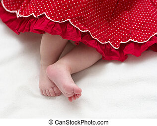 Newborn baby girl feet in red dress