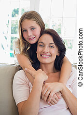 Girl embracing mother from behind at home