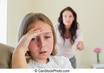 Girl with mother scolding her in background