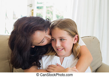 Mother kissing cute daughter on sofa