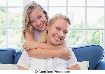 Girl embracing mother from behind in living room