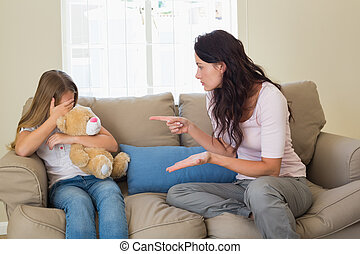 Woman pointing at scared daughter on sofa - Young woman...