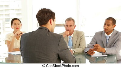 Businessman being interviewed by tough panel at the office