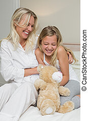 Mother tickling daughter in bed - Happy mother tickling...