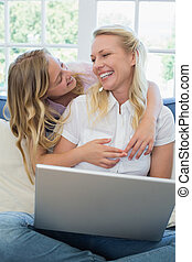 Woman with laptop looking at daughter