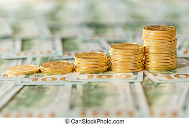 Gold coins stacked on new design 100 dollar bills - Stack of...