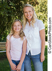 Mother with arm around daughter standing in park - Portrait...