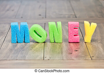Money in foam capital letters on a wooden surface
