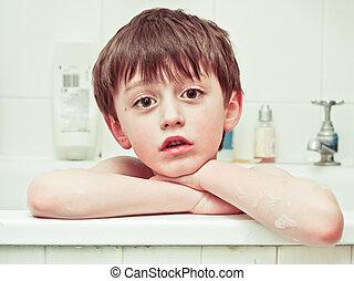 Bathtime - A six year old boy in the bath with a sad...