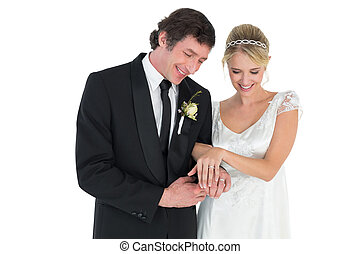 Newlywed couple looking at wedding rings - Happy newlywed...