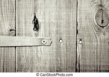 Hinge - Close up of a hinge on a wooden door in monochrome