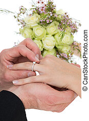 Cropped image of groom and bride exchanging ring - Cropped...