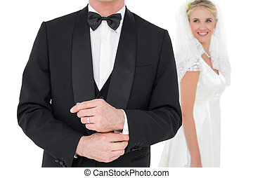 Groom adjusting tuxedo sleeve while bride looking at him -...