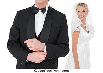 Bride looking at groom adjusting sleeve - Happy bride...
