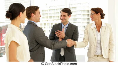 Business people shaking hands at interview while others...