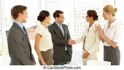 Business people shaking hands at interview while others clap...