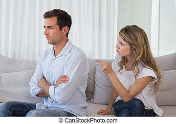 Couple having an argument in living room - Unhappy couple...