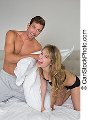Semi nude young couple pillow fighting in bed - Cheerful...