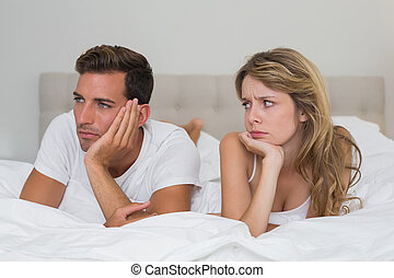 Couple not talking after an argument in bed - Unhappy couple...