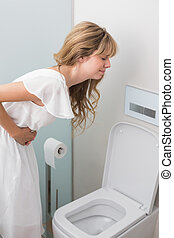 Woman with stomach sickness about to vomit into toilet -...