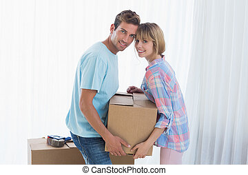 Happy couple carrying cardboard box in new house - Side view...