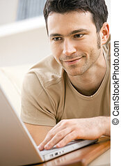 Man using laptop computer at home - Casual man wearing beige...