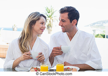 Couple looking at each other while having breakfast