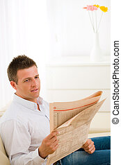Man reading newspaper - Casual man wearing white shirt and...