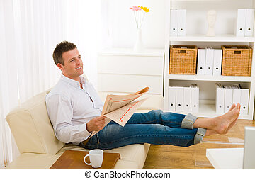 Man reading newspaper on couch - Casual man wearing white...
