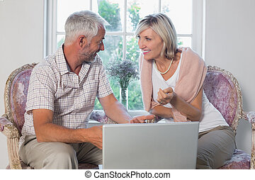 Couple discussing while using laptop at home - Happy mature...