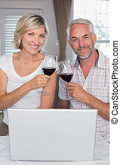 Happy mature couple toasting wine glasses at home - Portrait...