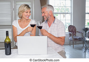 Mature couple toasting wine glasses at home - Happy mature...