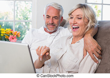 Mature couple using laptop at home - Cheerful relaxed mature...