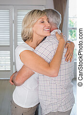 Mature couple embracing at home - Side view of a mature...