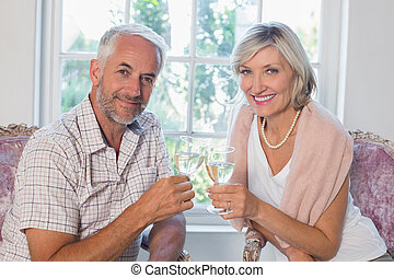 Happy mature couple with wine glasses at home - Portrait of...