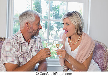 Happy mature couple with wine glasses at home - Happy loving...