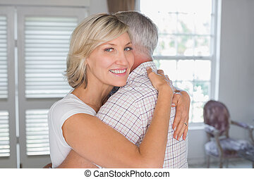 Mature couple embracing at home - Side view portrait of a...