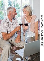 Mature couple with wine glasses at home - Happy mature...