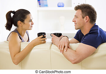 Couple talking at home - Adult couple sitting on sofa at...