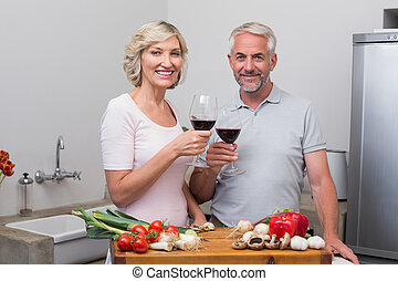 Mature couple toasting wine glasses - Happy mature couple...