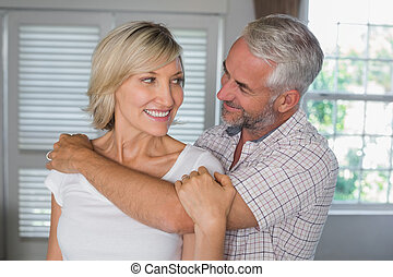 Mature man embracing a happy woman from behind at home