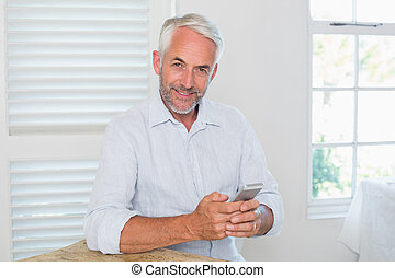 Relaxed mature man text messaging at home