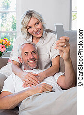 Mature couple photographing themselves with cellphone -...
