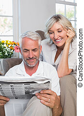 Mature couple reading newspaper - Happy mature couple...