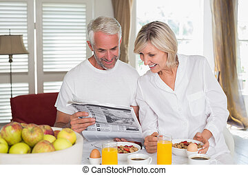 Couple reading newspaper at breakfa - Mature couple reading...
