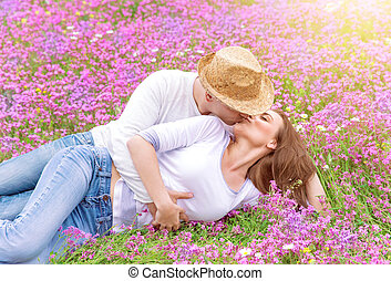 Kisses on spring meadow - Beautiful cheerful couple lying...