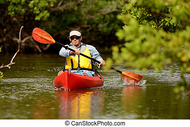 Man paddling in a kayak in Florida - Man paddling in a red...