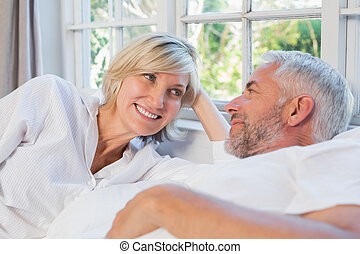 Smiling relaxed mature couple lying in bed at home -...